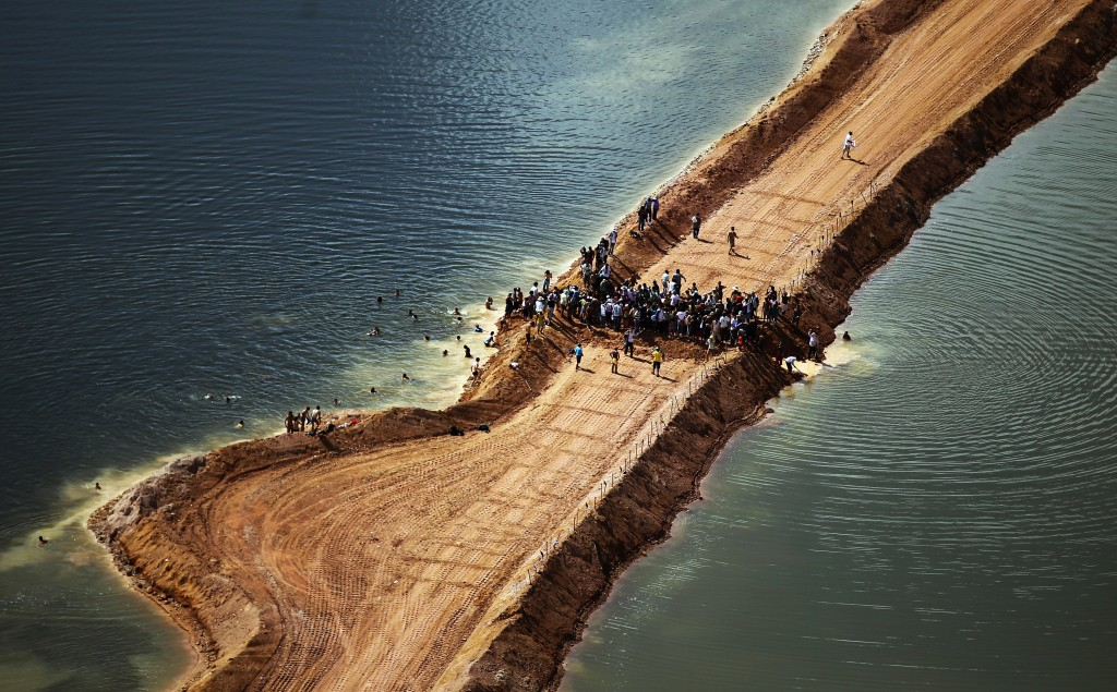 NEAR ALTAMIRA, BRAZIL - JUNE 15:  Residents who are being displaced by the Belo Monte dam and supporters stand atop a temporary earthen dam at the construction site after removing a strip of earth to restore the flow of the Xingu River as a protest against the construction on June 15, 2012 near Altamira, Brazil. Belo Monte will be the world's third-largest hydroelectric project and will displace up to 20,000 people while diverting the Xingu River and flooding as much as 230 square miles of rainforest. The controversial project is one of around 60 hydroelectric projects Brazil has planned in the Amazon to generate electricity for its rapidly expanding economy. While environmentalists and indigenous groups oppose the dam, many Brazilians support the project. The Brazilian Amazon, home to 60 percent of the world's largest forest and 20 percent of the Earth's oxygen, remains threatened by the rapid development of the country. The area is currently populated by over 20 million people and is challenged by deforestation, agriculture, mining, a governmental dam building spree, illegal land speculation including the occupation of forest reserves and indigenous land and other issues. Over 100 heads of state and tens of thousands of participants and protesters will descend on Rio de Janeiro, Brazil, later this month for the Rio+20 United Nations Conference on Sustainable Development or 'Earth Summit'. Host Brazil is caught up in its own dilemma between accelerated growth and environmental preservation.  (Photo by Mario Tama/Getty Images)