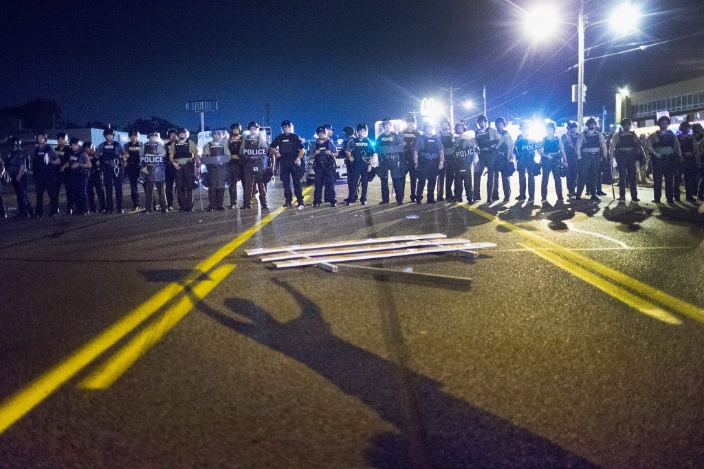 FERGUSON, MO - AUGUST 10:  Police stand guard as demonstrators, marking the one-year anniversary of the shooting of Michael Brown, protest along West Florrisant Street on August 10, 2015 in Ferguson, Missouri. Mare than 100 people were arrested today during protests in Ferguson and the St. Louis area. Brown was shot and killed by a Ferguson police officer on August 9, 2014. His death sparked months of sometimes violent protests in Ferguson and drew nationwide focus on police treatment of black suspects.  (Photo by Scott Olson/Getty Images)