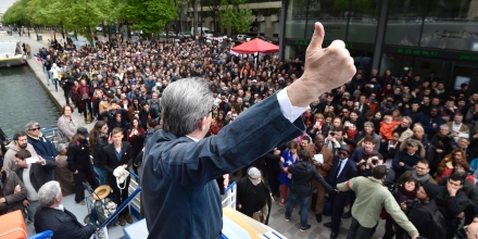 French presidential election candidate for the far-left coalition La France insoumise Jean-Luc Melenchon gestures as he gives a speech aboard an