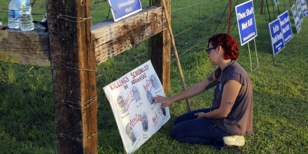 Gina Grimm, daughter of inmate Jack Jones, touches a poster of those condemned to be executed outside the Varner Unit on Monday, April 24, 2017 near Varner, Ark.    Jack Jones and Marcel Williams received lethal injections on the same gurney Monday night, just about three hours apart. It was the first double execution in the United States since 2000.   (Stephen B. Thornton/The Arkansas Democrat-Gazette via AP)