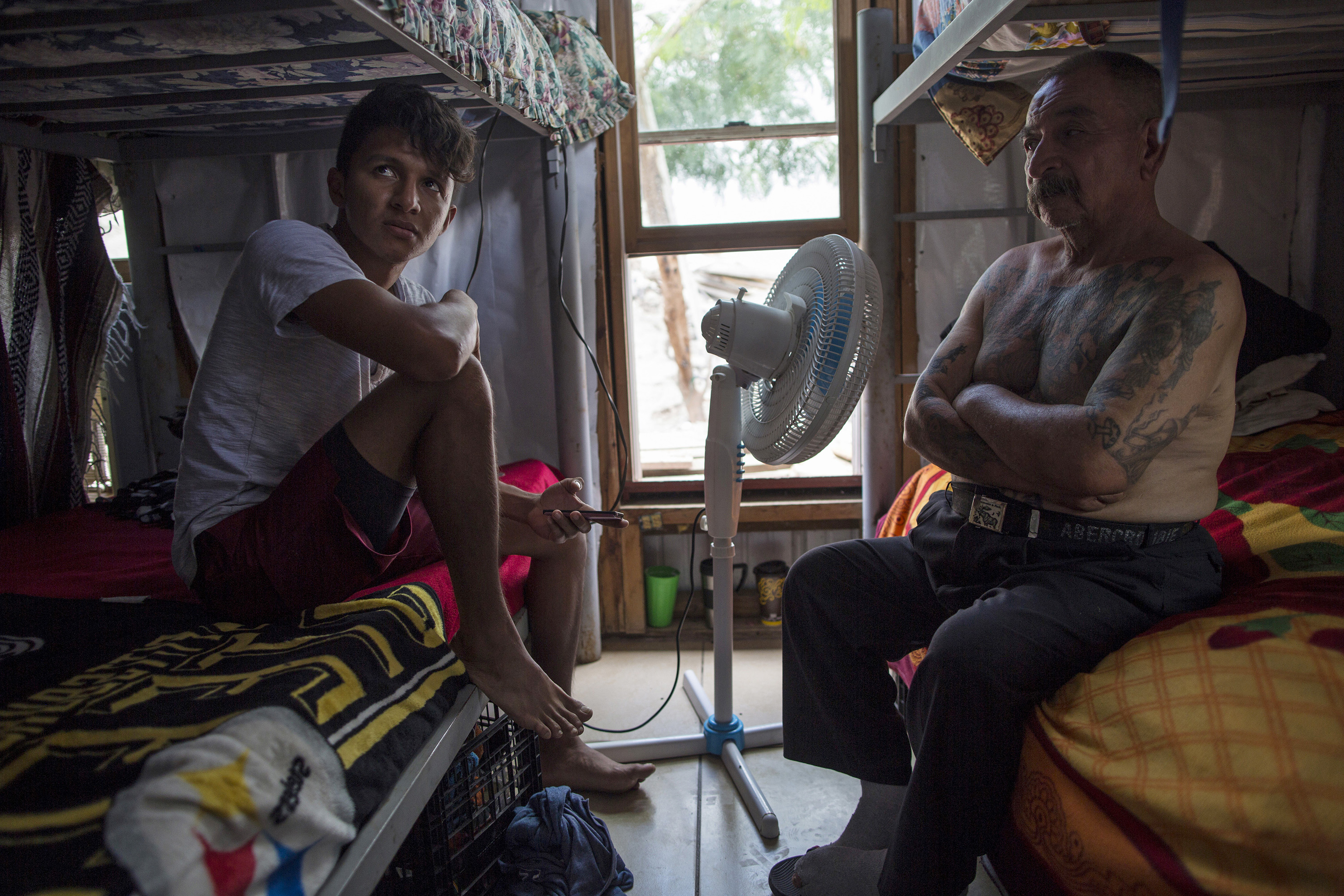 "Migrants Juan Parras, 65, right, and Junior Matute, 19, rest on their beds at the migrant shelter ""Senda de Vida"" in Reynosa, Mexico, Wednesday, March, 22, 2017. Matute said his brother was deported from the United States to Honduras and then murdered in February 2016. ""I come for a reason. It's not like one day I just decided to leave my country,"" he says.  Parras said he was deported one year ago from California, where he left behind three sons, and that he plans to try to return. (AP Photo/Rodrigo Abd)"