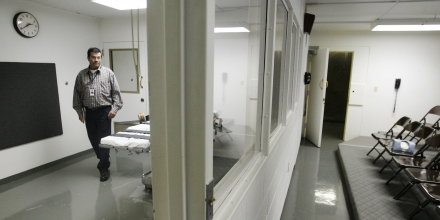 FILE - In this Tuesday, April 15, 2008 file photo, Terry Crenshaw, warden's assistant at the Oklahoma State Penitentiary, walks past a gurney in the execution chamber in McAlester, Okla. At right are rows of chairs for witnesses. A lawsuit filed on behalf of 21 Oklahoma death row inmates on Wednesday, June 25, 2014, seeks to halt any attempt to execute them using the state's current lethal injection protocols, which it claims presents a risk of severe pain and suffering. (AP Photo)