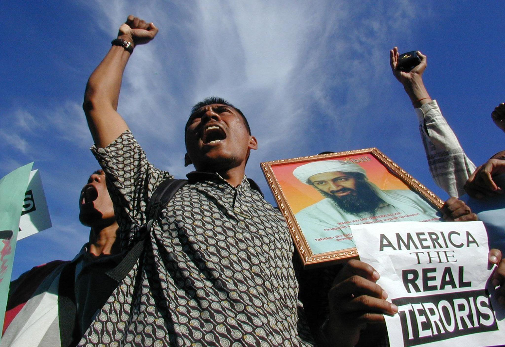 """BANDA ACEH, INDONESIA:  A Muslim protestor holding a portrait of Saudi-dissident Osama bin Laden shout """"Allah Akbar"""" during a protest in front of Baiturrahman mosque, Banda Aceh, 10 October 2001. The demonstrators are protesting against the US-led military strikes against Afghanistan.       AFP PHOTO (Photo credit should read AFP/Getty Images)"""