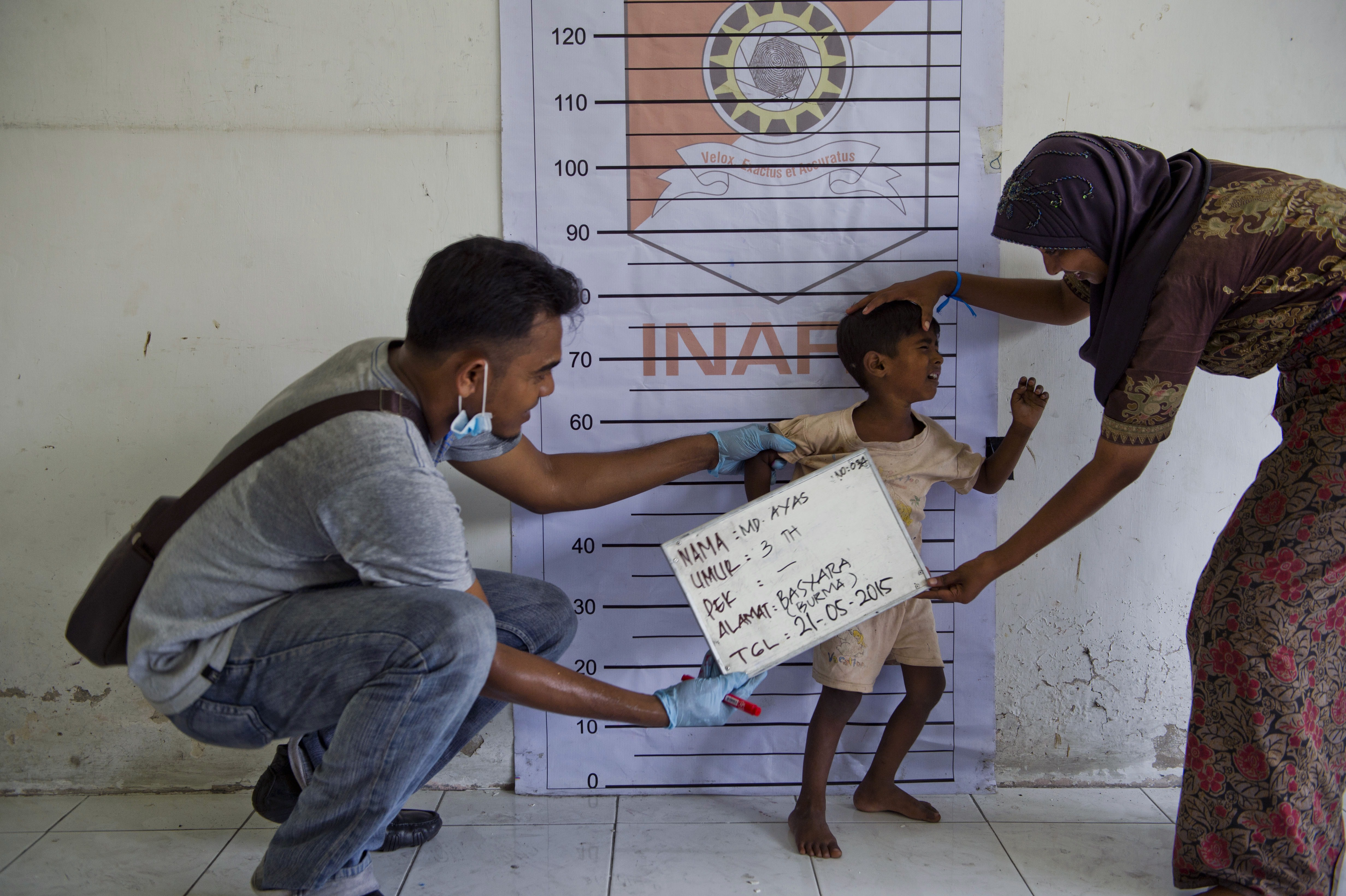"""To go with """"SEAsia migrants Indonesia"""", Focus by Olivia RondonuwuIn this picture taken on May 21, 2015, a Rohingya boy (C) from Myanmar is photographed during police identification procedures at a newly set up confinement area in Bayeun, Aceh province after more than 400 Rohingya migrants from Myanmar and Bangladesh were rescued by Indonesian fishermen off the waters of the province on May 20. Boat people who have come ashore in Southeast Asia after harrowing journeys are delighted that Indonesia and Malaysia will give them temporary shelter -- although some were baffled by an offer of sanctuary in a tiny African nation they had never heard of. There was some confusion over an offer from the impoverished West African nation of Gambia to take in all Rohingya migrants as part of its """"sacred duty"""" to alleviate the suffering of fellow Muslims. AFP PHOTO / ROMEO GACAD (Photo credit should read ROMEO GACAD/AFP/Getty Images)"""