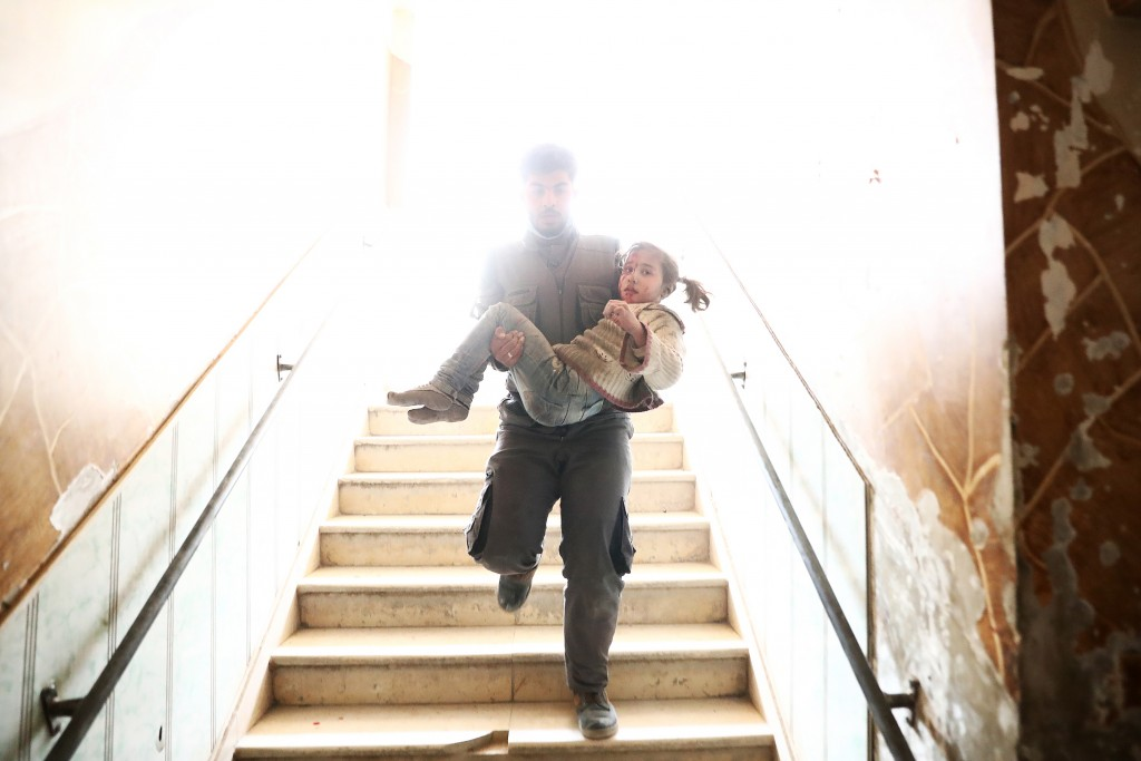 TOPSHOT - A Syrian civil defence volunteer carries a wounded girl as he rushes to a make-shift hospital following reported government airstrike on the rebel-held town of Douma, on the eastern outskirts of the capital Damascus, on February 25, 2017.&lt;br /&gt;&lt;br /&gt;&lt;br /&gt;<br /> Syrian regime forces carried out raids on several areas in the country, targeting mainly the besieged town of Douma, causing the deaths of at least 13 civilians, according to Syrian Observatory for Human Rights. The raids continued despite the United Nations confirmation a few days earlier that Moscow formally asked its ally Damascus to stop launching strikes during the Geneva negotiations, which began earlier in the week. / AFP / Abd Doumany        (Photo credit should read ABD DOUMANY/AFP/Getty Images)