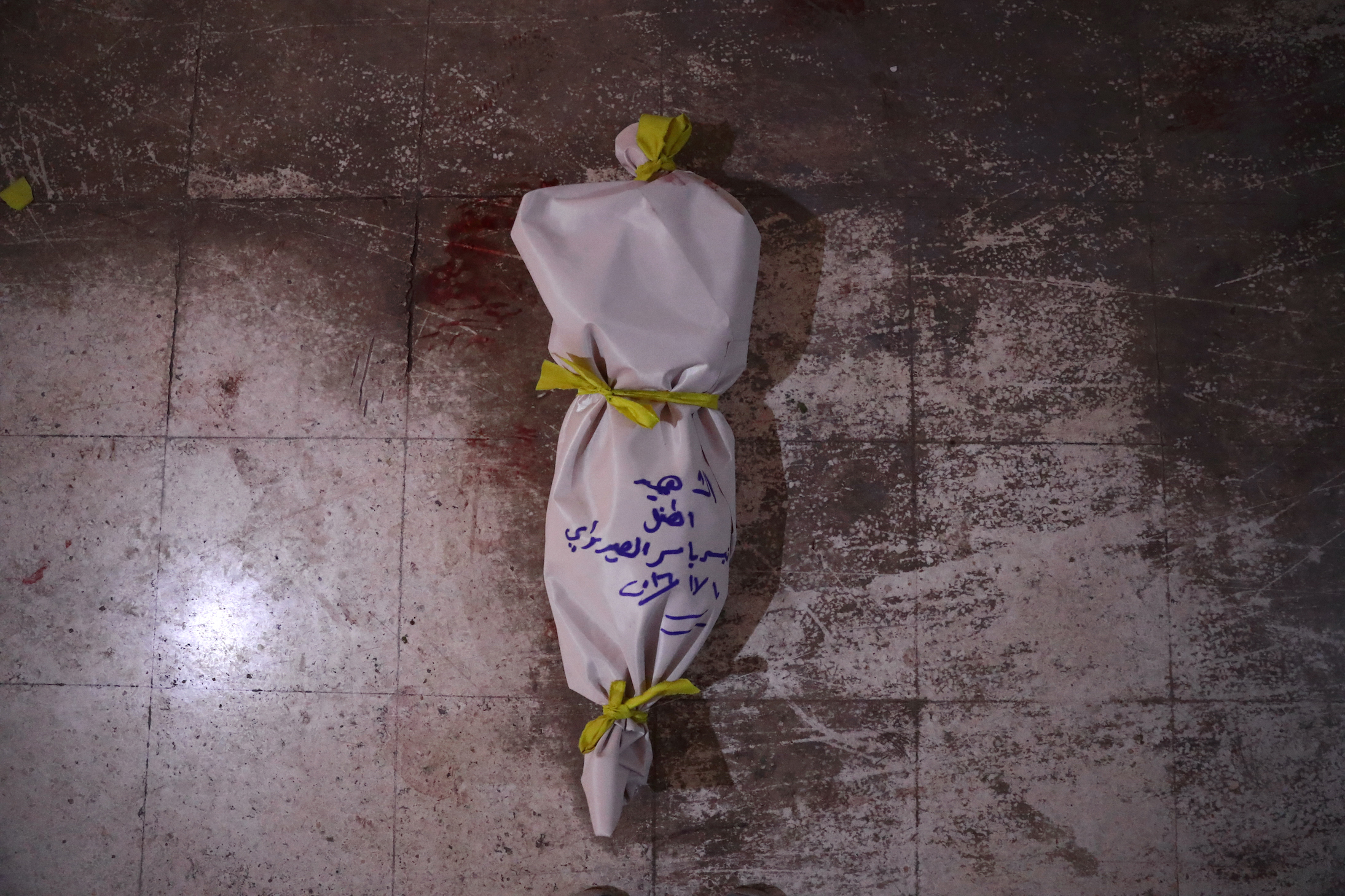 TOPSHOT - The body of a victim lies on the floor at a make-shift morgue following an airstrike in the rebel-held town of Douma, on the eastern outskirts of the capital Damascus, on November 10, 2016.At least 11 people including four children were killed on November 10 in air strikes on rebel-held areas near the Syrian capital, with one strike on the besieged town of Douma killing eight people including three children, according to the Syrian Observatory for Human Rights. / AFP / Abd Doumany (Photo credit should read ABD DOUMANY/AFP/Getty Images)