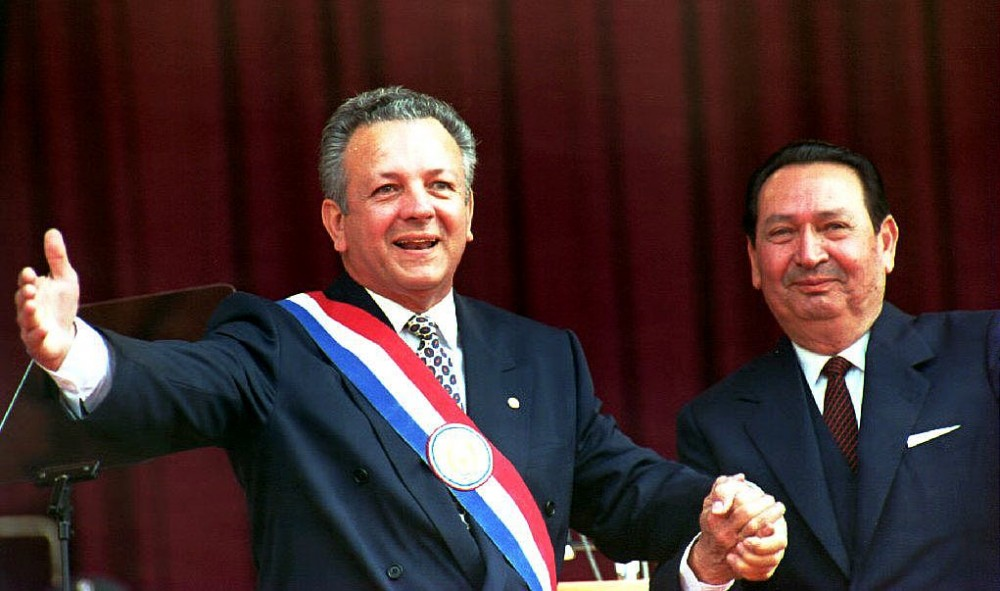 ASUNCION, PARAGUAY - AUGUST 15:  Paraguayan newly-sworn in President Juan Carlos Wasmosy (L) acknowledges the applause 15 August 1993 after receiving the presidential sash from his predecessor Andres Rodriguez (R) during the inauguration ceremony. Wasmosy, a 54-year-old businessman of Hungarian descent, becomes Paraguay's first democratically-elected civilian president in half a century.  (Photo credit should read NORBERTO DUARTE/AFP/Getty Images)