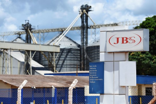 """View of the JBS-Friboi Logo at the chicken processing plant entrance, in Samambaia, Federal District, Brazil on March 17, 2017.<br /> Brazilian Federal police have dismantled, after two years of running the """"weak flesh"""" operation, a vast network of adulterated food, involving major meat processing plants and inspectors who accepted bribes to approve products in bad condition for domestic consumption and exportation.  / AFP PHOTO / EVARISTO SA        (Photo credit should read EVARISTO SA/AFP/Getty Images)"""