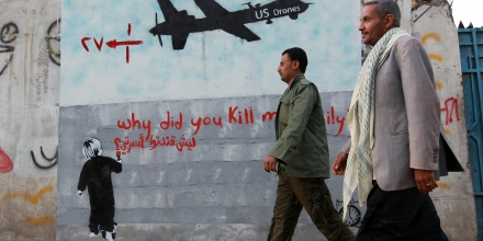 Yemeni men walk past a mural depicting a US drone and reading