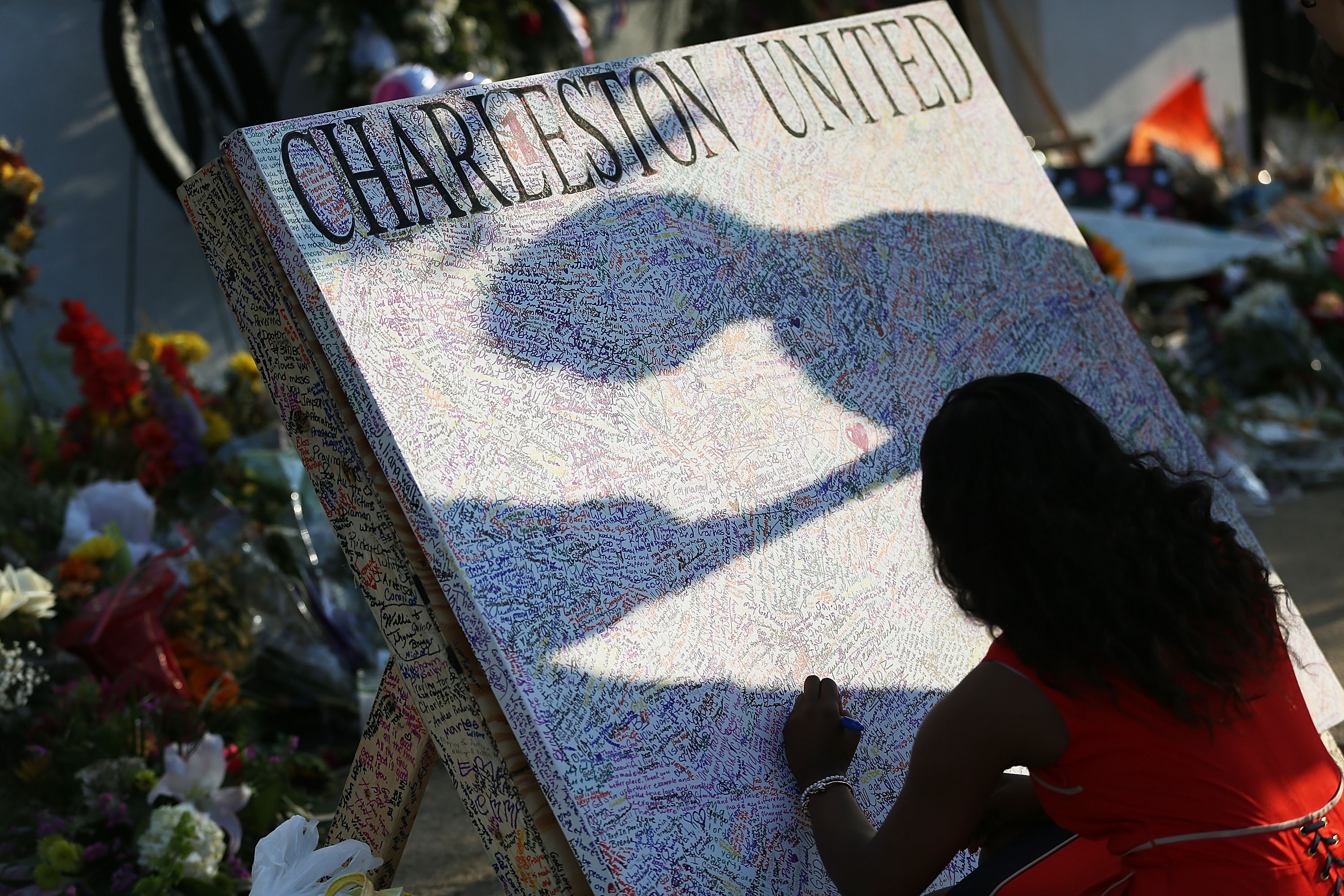 CHARLESTON, SC - JUNE 22:  Alana Simmons leaves a message on a board set up in front of the Emanuel African Methodist Episcopal Church after a mass shooting at the church killed nine people, on June 22, 2015. 21-year-old Dylann Roof is suspected of killing nine people during a prayer meeting in the church in Charleston, which is one of the nation's oldest black churches. (Photo by Joe Raedle/Getty Images)