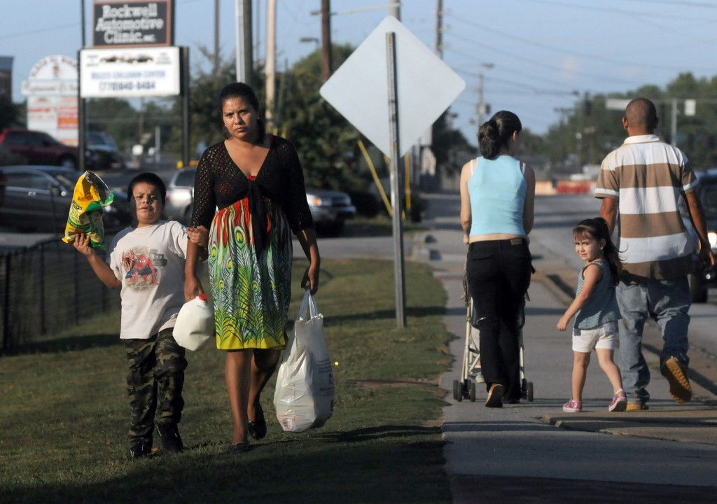 In this photo taken Thursday Sept. 30, 2011, undocumented immigrants from Mexico, Fredy and Anahi Martinez, right, walk with their two children to the supermarket in Norcross, Ga. The couple has been in the United States for the past 12 years and say they would risk deportation if they drove a car without a driver's license because of the enforcement of the 287(g) program in their community, which allows state and local law enforcement agencies to question anyone on their immigration status for any infraction of the law such as driving without a license. (AP Photo/Erik S. Lesser)