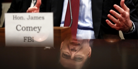 FBI Director James Comey is seen in a reflection as he testifies in a House Appropriations hearing on