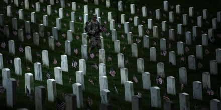 A soldier in the Old Guard places flags at graves in Arlington National Cemetery during