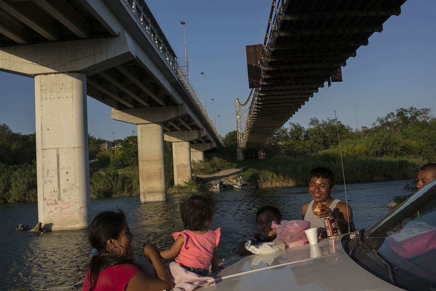 "FILE - This March 22, 2017, file photo shows a family having a picnic on the bank of the Rio Grande river in Miguel Aleman, Tamaulipas state, Mexico, located across from Roma, Texas. President Donald Trump will face many obstacles in building his ""big, beautiful wall"" on the U.S.-Mexico border, including how to pay for it and how to contend with unfavorable geography and the legal battles ahead.  (AP Photo/Rodrigo Abd, File)"