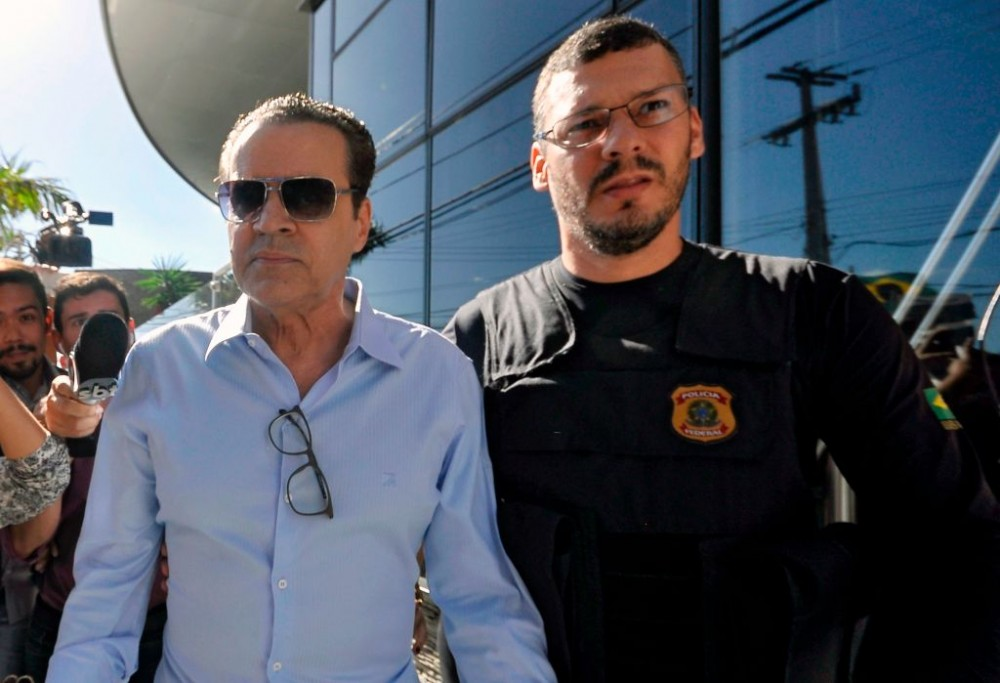 "Former Brazil's Tourism Minister Henrique Eduardo Alves (L) is escorted by a Federal Police agent after being arrested at his residence in Natal, Rio Grande do Norte state, Northeast of Brazil, on June 6, 2017.Alves is accused of being involved in corruption during the construction of one of the ten stadiums Brazil buildt for the 2014 FIFA World Cup, the Arena das Dunas Stadium in Natal. / AFP PHOTO / Tribuna do Norte / MAGNUS NASCIMENTO / Brazil OUT / RESTRICTED TO EDITORIAL USE - MANDATORY CREDIT ""AFP PHOTO /Tribuna do Norte /HO "" - NO MARKETING - NO ADVERTISING CAMPAIGNS - DISTRIBUTED AS A SERVICE TO CLIENTS (Photo credit should read MAGNUS NASCIMENTO/AFP/Getty Images)"