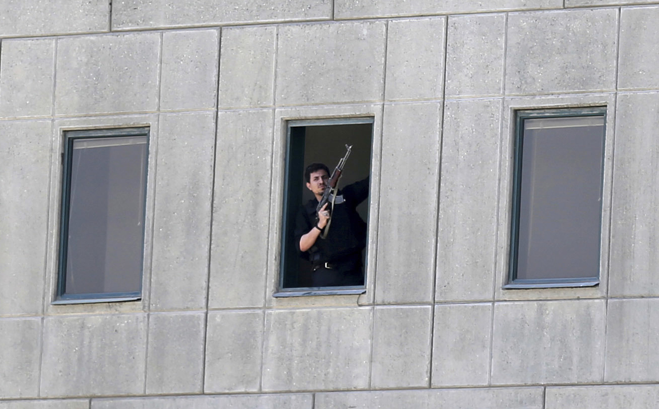 An armed man stands in a window of the parliament building in Tehran, Iran, Wednesday, June 7, 2017. Several attackers stormed into Iran's parliament and a suicide bomber targeted the shrine of Ayatollah Ruhollah Khomeini on Wednesday, killing a security guard and wounding several other people in rare twin attacks, with the shooting at the legislature still underway. (Fars News Agency, Omid Vahabzadeh via AP)