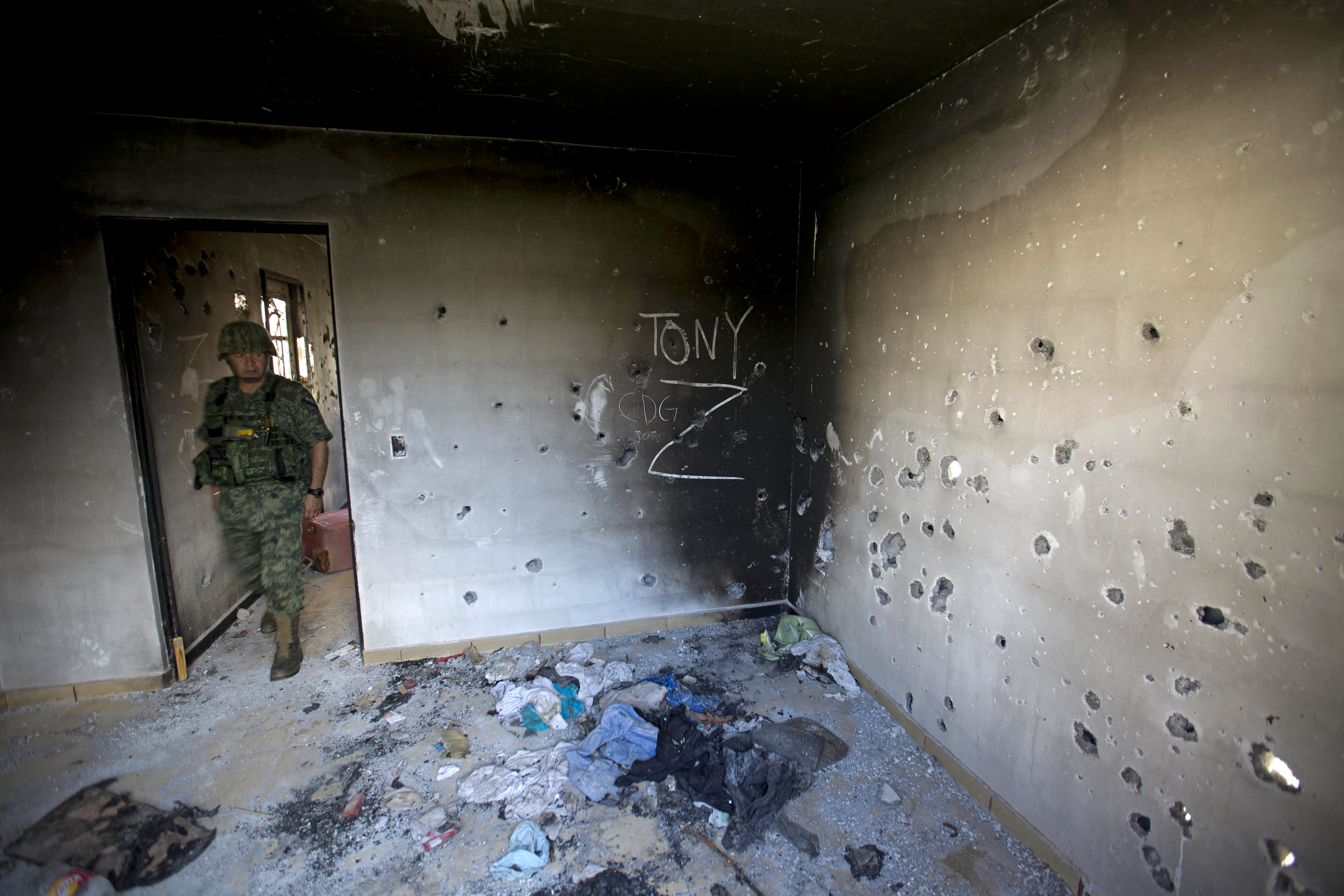 FILE - In this Sept. 6, 2014 file photo, a soldier enters a bullet-riddled home, tagged with the initials CDG for the Gulf Cartel, and Z for Zetas, in Ciudad Victoria, in Mexico's state of Tamaulipas. The country's war on drugs has changed the nature and map of Mexican cartels. One law enforcement official in the northern border state of Tamaulipas says he now routinely sees young cartel gunmen who not only have few regrets: they actually see killing as the best professional path they can take. (AP Photo/Eduardo Verdugo, File)