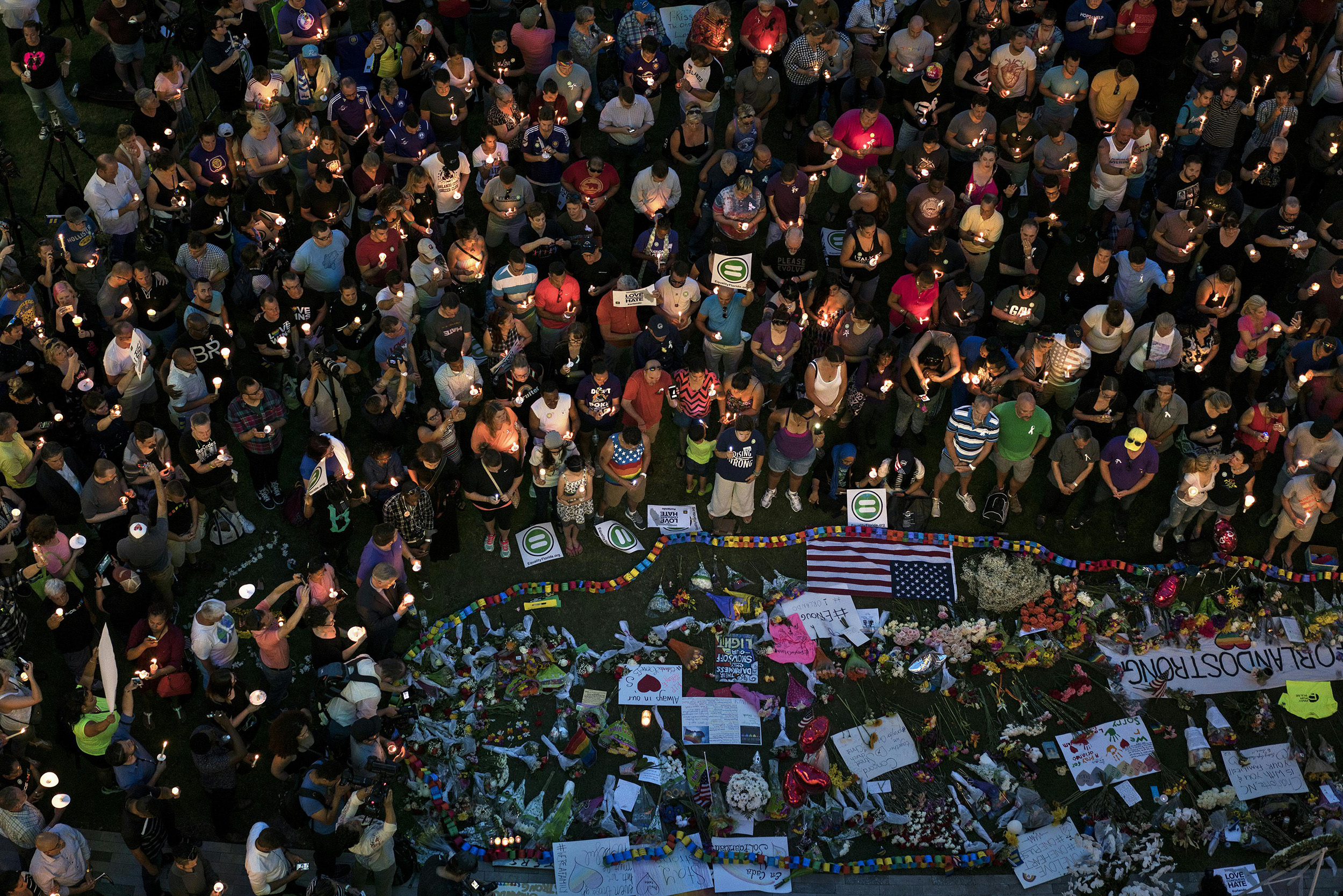 TOPSHOT - Mourners hold candles while observing a moment of silence during a vigil outside the Dr. Phillips Center for the Performing Arts for the mass shooting victims at the Pulse nightclub June 13, 2016 in Orlando, Florida.The American gunman who launched a murderous assault on a gay nightclub in Orlando was radicalized by Islamist propaganda, officials said Monday, as they grappled with the worst terror attack on US soil since 9/11. / AFP / Brendan Smialowski (Photo credit should read BRENDAN SMIALOWSKI/AFP/Getty Images)