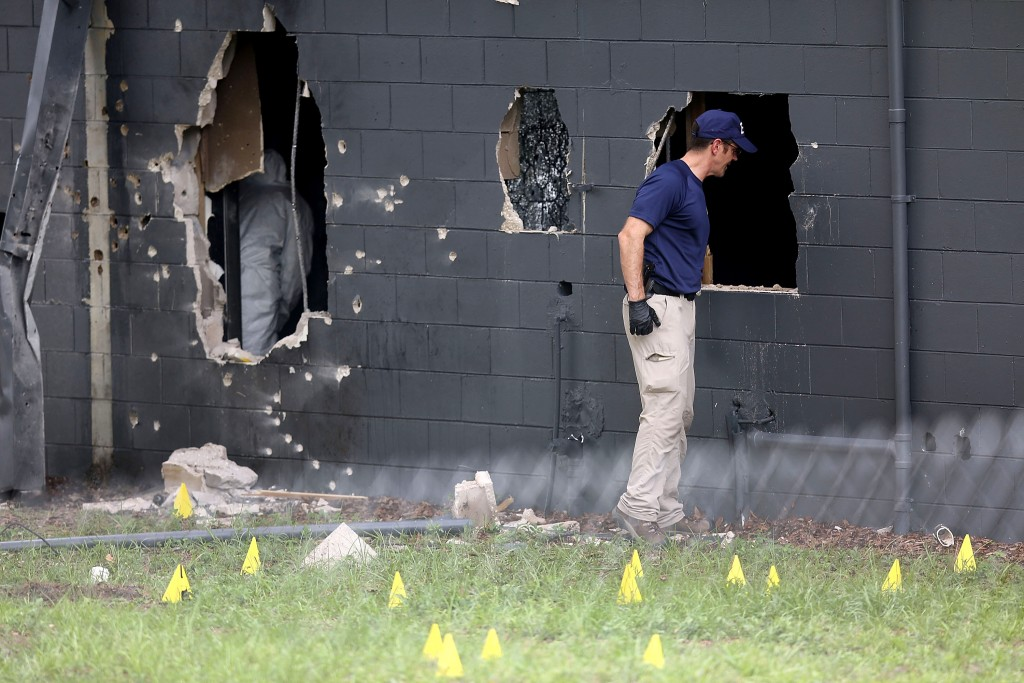 ORLANDO, FL - JUNE 12:  FBI agents investigate the damaged rear wall of the Pulse Nightclub where Omar Mateen allegedly killed at least 50 people on June 12, 2016 in Orlando, Florida. The mass shooting killed at least 50 people and injured 53 others in what is the deadliest mass shooting in the country's history.  (Photo by Joe Raedle/Getty Images)