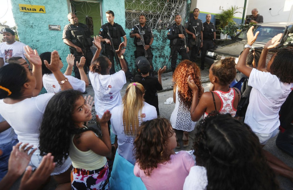 RIO DE JANEIRO, BRAZIL - JULY 06:  Protestors chant in front of police officers following the funeral of Vanessa dos Santos, 10, who was shot in the head and killed in the doorway of her house during a shootout involving police and gang members in the Lins favela community, on July 6, 2017 in Rio de Janeiro, Brazil. Protestors stopped traffic along a main highway while marching back to the Lins favela following the funeral. In the week leading up to her death, there were at least 168 shootings reported in Rio, according to Fogo Cruzado, an app created by Amnesty International Brazil. Violence has spiked in many of the city's favelas in the midst of an economic crisis.  (Photo by Mario Tama/Getty Images)