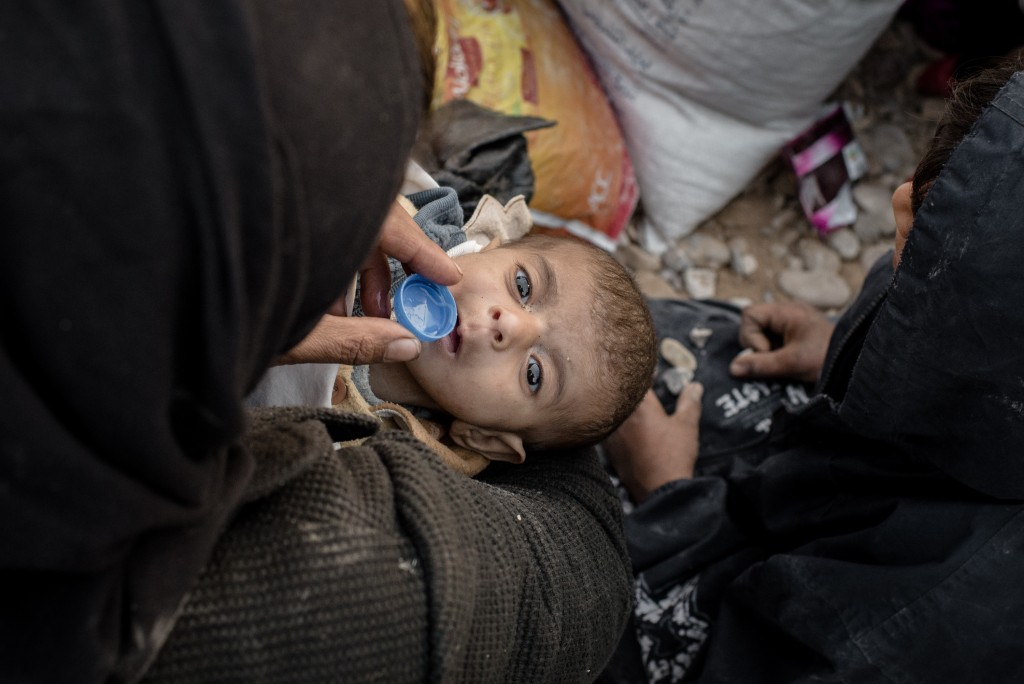 A woman gives her young child water while waiting to be let into the Hasansham camp for displaced persons on Nov. 4, 2016.