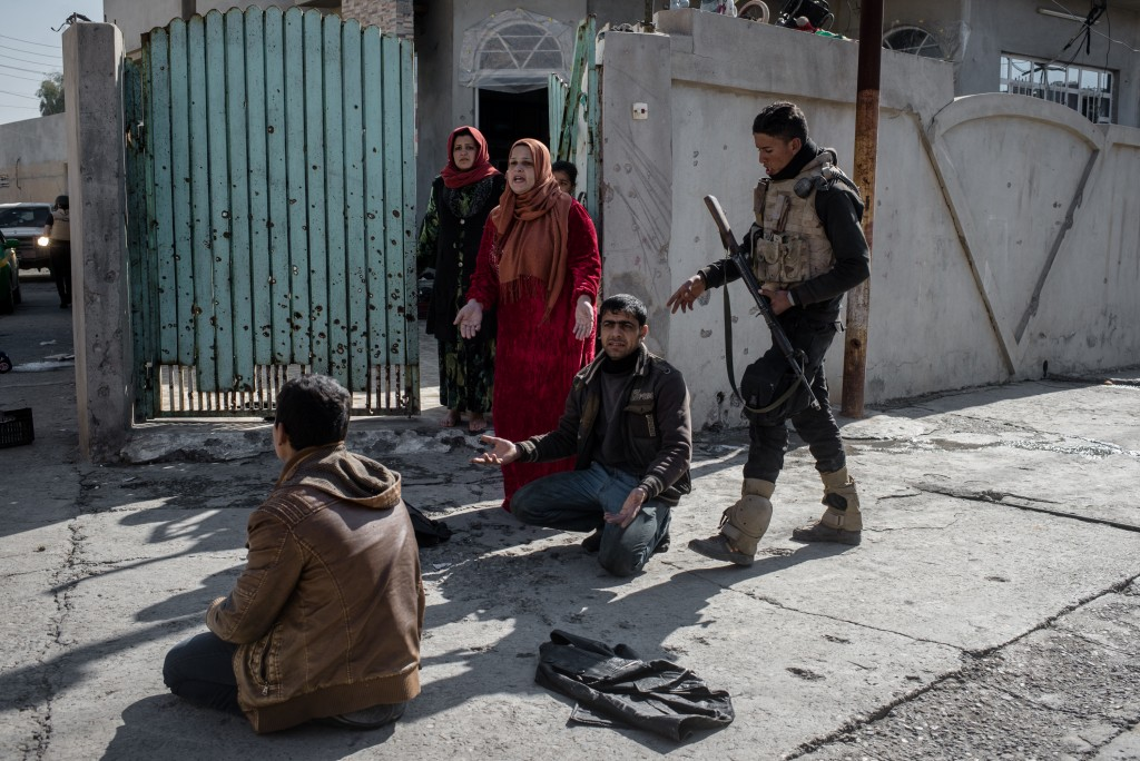 An officer with the Iraqi National Security Service (NSS) subdues civilians during a raid on suspected ISIS militants in eastern Mosul, Iraq on Feb. 21, 2017. The teenager facing away from the camera was arrested on suspected ISIS ties; the man on the right facing the camera was not arrested but was forced to the ground so he would not interfere.