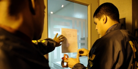 U.S. Marshals post a copy of the federal government's complaint on the door of the Razi school Thursday, Nov. 12, 2009 in the Queens borough of New York. The school was among the assets seized by the federal government in a civil complaint in federal court seeking the forfeiture of more than $500 million in assets of the Alavi Foundation and an alleged front company. Federal prosecutors Thursday took steps to seize four U.S. mosques and a Fifth Avenue skyscraper owned by a nonprofit Muslim organization long suspected of being secretly controlled by the Iranian government. (AP Photo/Stephen Chernin)