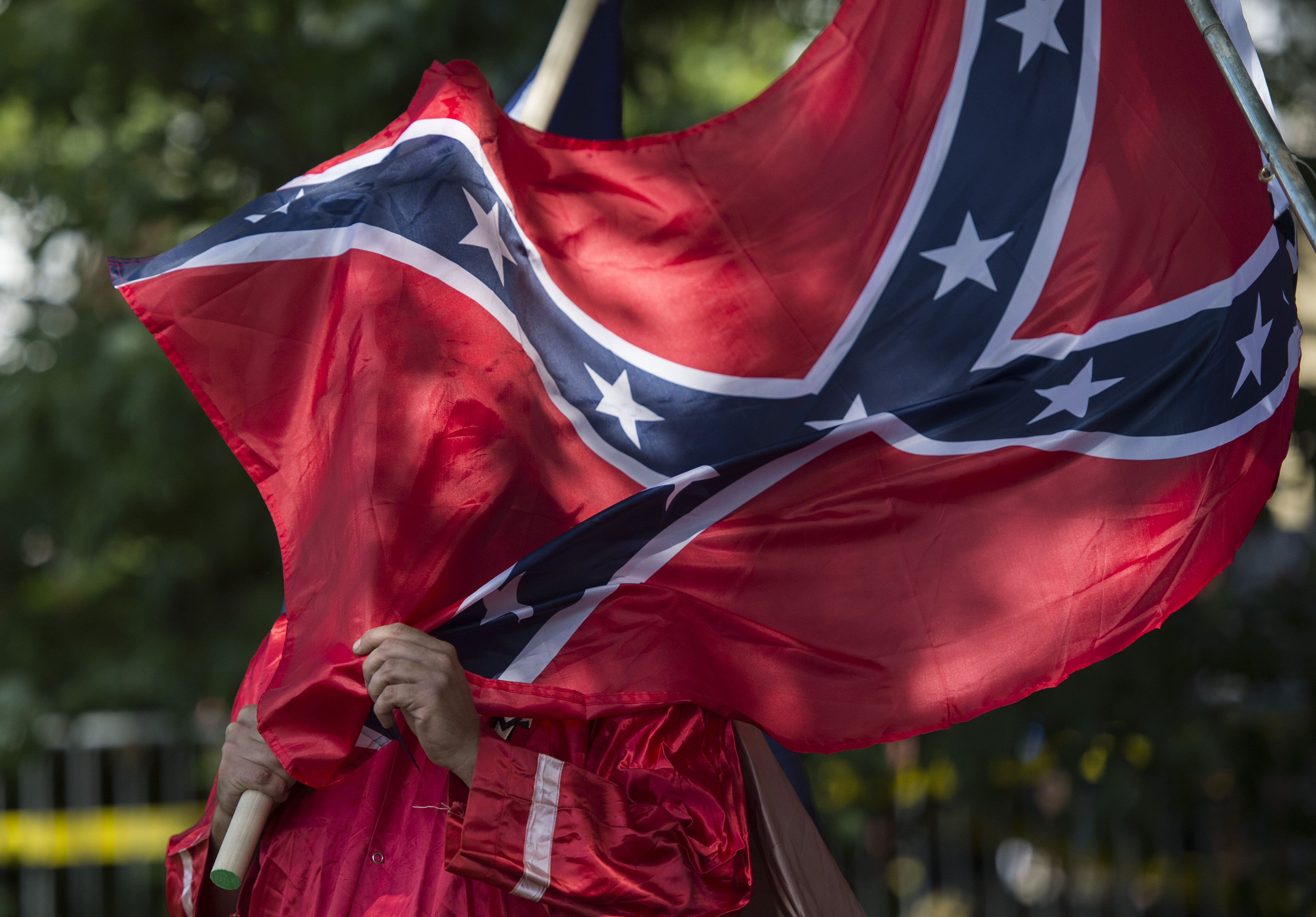 A member of the Ku Klux Klan holds a Confederate flag over his face during a rally, calling for the protection of Southern Confederate monuments, in Charlottesville, Virginia on July 8, 2017.The afternoon rally in this quiet university town has been authorized by officials in Virginia and stirred heated debate in America, where critics say the far right has been energized by Donald Trump's election to the presidency. / AFP PHOTO / ANDREW CABALLERO-REYNOLDS (Photo credit should read ANDREW CABALLERO-REYNOLDS/AFP/Getty Images)