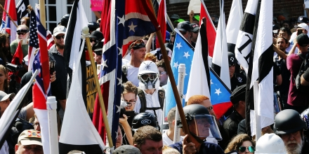 White nationalist demonstrators walk into the entrance of Lee Park surrounded by counter demonstrators in Charlottesville, Va., Saturday, Aug. 12, 2017. Gov. Terry McAuliffe declared a state of emergency and police dressed in riot gear ordered people to disperse after chaotic violent clashes between white nationalists and counter protestors. (AP Photo/Steve Helber)