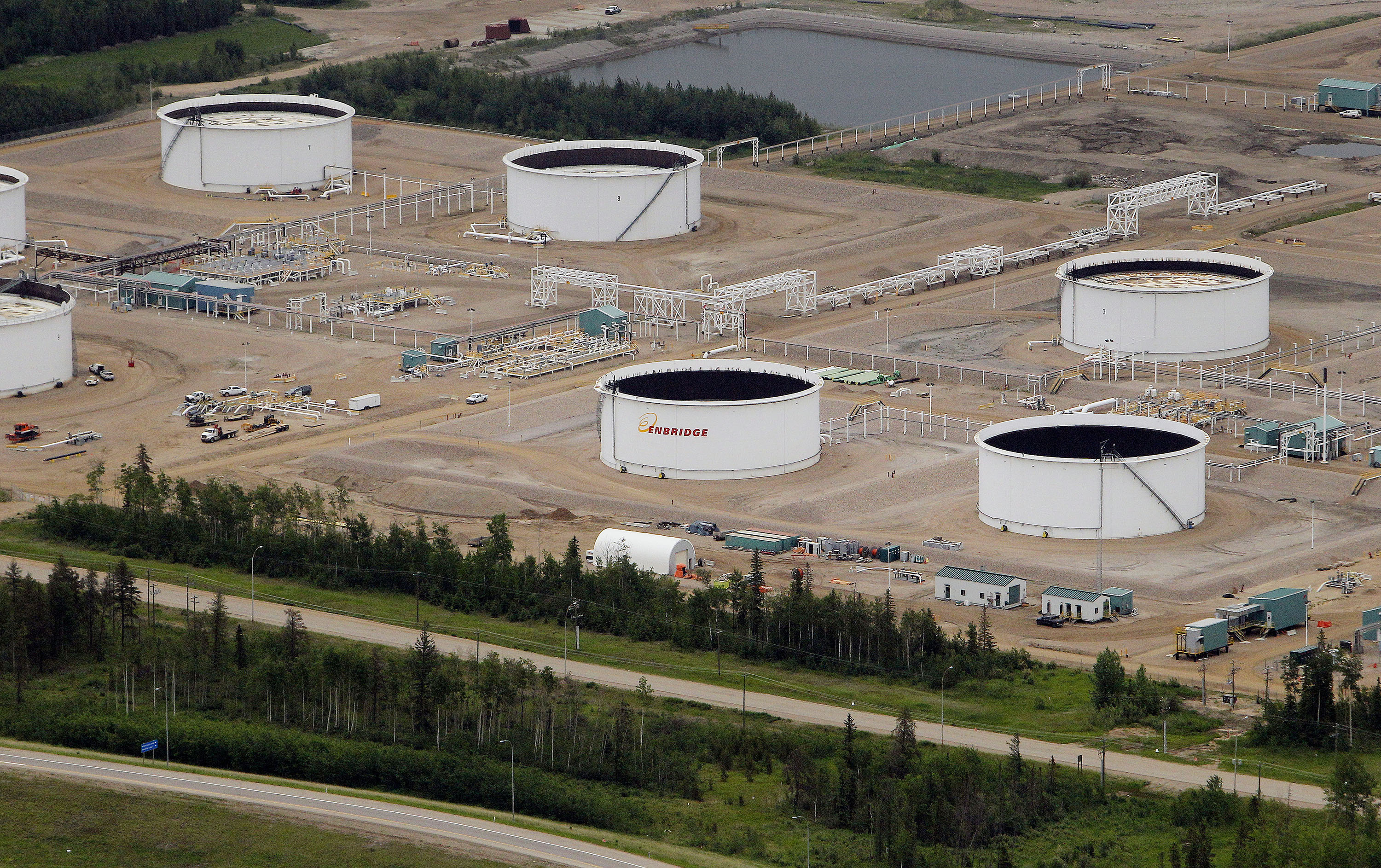 An Enbridge Inc. tank farm stands in this aerial photograph taken above the Athabasca Oil Sands near Fort McMurray, Alberta, Canada, on Wednesday, June 19, 2014. Heavy crude from the oil sands has traded at an average of $18.70 per barrel below the U.S. benchmark over the last five years due to a transportation bottleneck in North America. The discount costs Canadas economy as much as C$50 million per day, according to the Canadian Chamber of Commerce. Photographer: Ben Nelms/Bloomberg via Getty Images