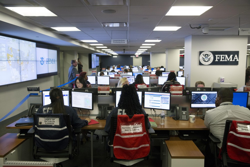 WASHINGTON, DC - AUGUST 4: (AFP OUT) Employees sit in front of computer monitors at the command center of the Federal Emergency Management Agency (FEMA) headquarters, shortly before a visit by U.S. President Donald Trump (not pictured) on August 4, 2017 in Washington, DC. Trump visited FEMA headquarters to receive a briefing on the hurricane season. (Photo by Michael Reynolds - Pool/Getty Images)