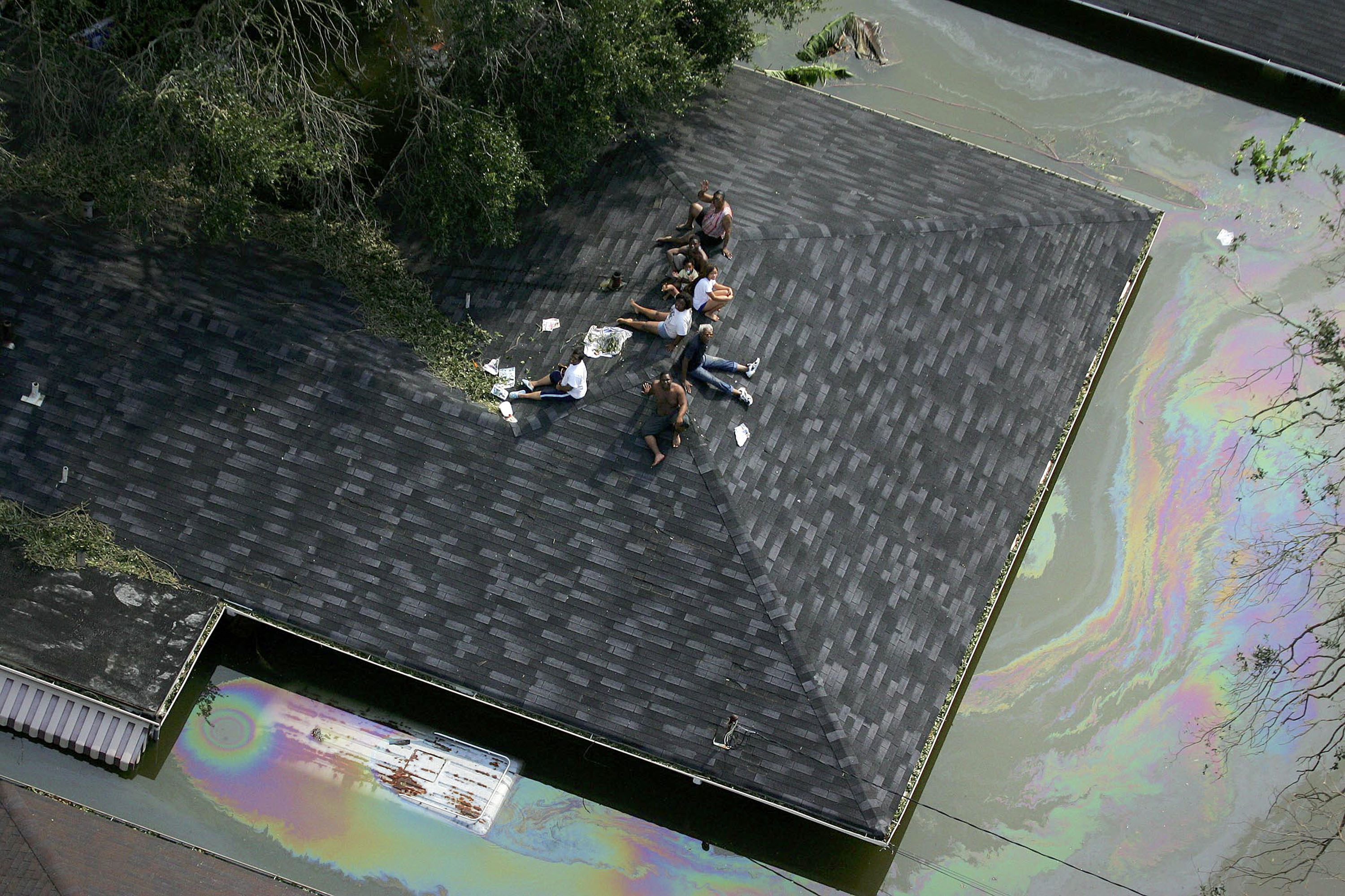 People are stranded on a roof due to flood waters from Hurricane Katrina 30 August 2005 in New Orleans, Louisiana. It is estimated that 80 percent of New Orleans is under flood waters as levees begin to break and leak around Lake Ponchartrain.   AFP PHOTO/POOL/Vincent Laforet (Photo credit should read POOL/AFP/Getty Images)
