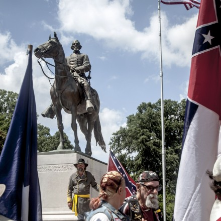 A Confederate battle flag is carried as people surround the statue of Nathan Bedford Forrest during a rally against removing the figure in Memphis, Tenn., July 12, 2015. This month, the Memphis City Council voted unanimously to begin an intricate process of removing the brass statue from the park ? along with the remains of Forrest and his wife, encased since 1905 in its marble base. (Andrea Morales/The New York Times)