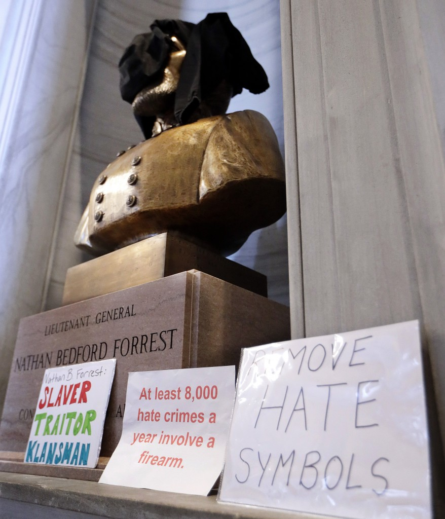 Signs stand in front of a bust of Nathan Bedford Forrest and a sweatshirt covers its face during a protest Monday, Aug. 14, 2017, in Nashville, Tenn. Protesters called for the removal of the bust, which is displayed in the hallway outside the House and Senate chambers. Violence in Virginia this weekend has given rise to a new wave of efforts to remove or relocate Confederate monuments. (AP Photo/Mark Humphrey)
