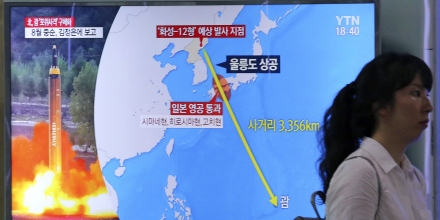 """A woman passes by a TV screen showing a local news program reporting on North Korea's threats to strike Guam with missiles at the Seoul Train Station in Seoul, South Korea, Thursday, Aug. 10, 2017. North Korea has announced a detailed plan to launch a salvo of ballistic missiles toward the U.S. Pacific territory of Guam, a major military hub and home to U.S. bombers. If carried out, it would be the North's most provocative missile launch to date. The signs at left top read """" North Korea announced a plan to launch a salvo of ballistic missiles toward the Guam. (AP Photo/Ahn Young-Joon)"""