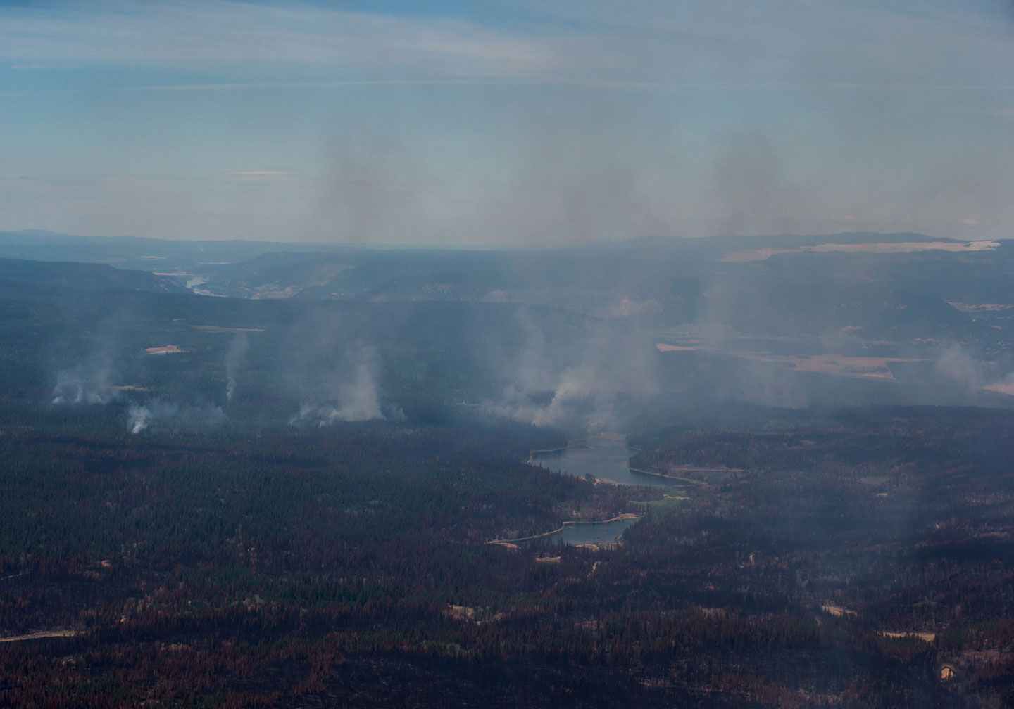 Smoke from wildfires fills the air and burned trees are seen in this aerial view from a Canadian Forces Chinook helicopter as Prime Minister Justin Trudeau views areas affected by wildfire near Williams Lake, British Columbia, on Monday, July 31, 2017. (Darryl Dyck/The Canadian Press via AP)