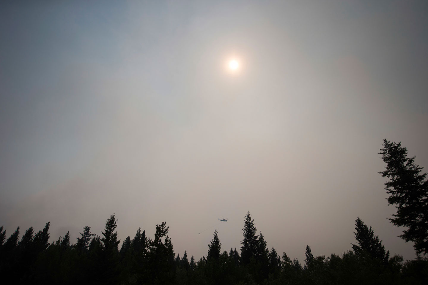 Smoke obscures the sun as a helicopter carrying a bucket battles the Gustafsen wildfire near 100 Mile House, B.C., on Saturday July 8, 2017. More than 180 fires were burning, many considered out of control, as the B.C. government declared a provincewide state of emergency to co-ordinate the crisis response. Officials said buildings have been destroyed, but they did not release numbers. The BC Wildfire Service says over 173 fires were reported on Friday alone as lightning storms rolled over several parts of B.C. (Darryl Dyck/The Canadian Press via AP)