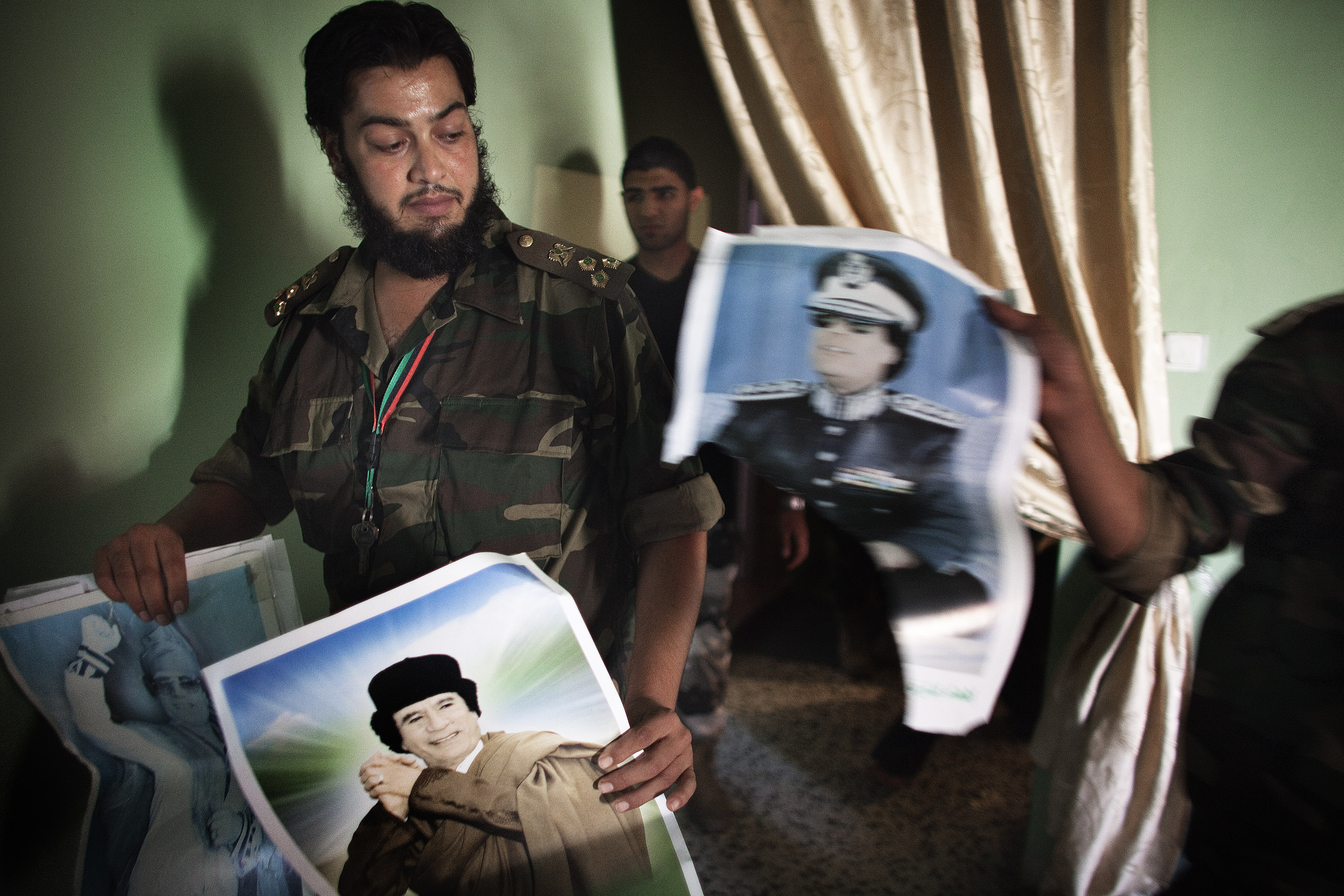 National Transitional Council (NTC) fighters confiscate posters of former Libyan leader Moammar Gadhafi in the apartment of a man suspected of being a loyalist in the restive Abu Salim district of Tripoli October 15, 2011. AFP PHOTO/MARCO LONGARI (Photo credit should read MARCO LONGARI/AFP/Getty Images)