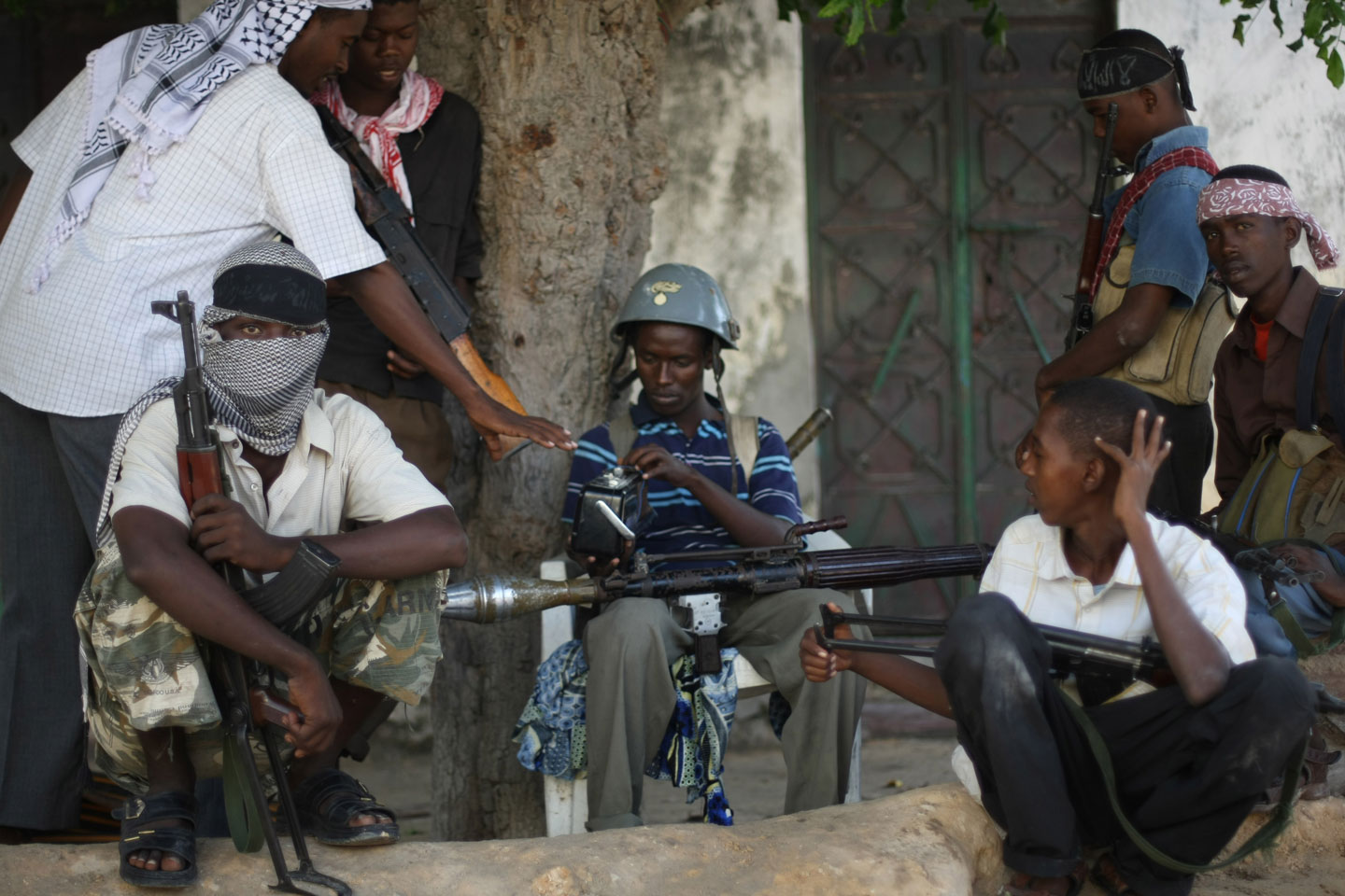 "Al-Shabab and Hizbul Islam militants take a break at a front-line section in sanca district in Mogadishu,  on July 21, 2009. Somalia's hard line Shabab militia yesterday raided the offices of three UN organisations hours after they banned their operations on accusation that they were ""enemies of Islam and Muslims. The armed group stormed the United Nations Development Programme, UN Department of Safety and Security and the UN Political Office for Somalia in two southern Somalia towns and impounded office equipment. The above foreign agencies have been found to be working against the benefit of the Somali Muslim population and against the establishment of an Islamic state in Somalia,"" the Shebab said in a statement. AFP PHOTO/ MOHAMED DAHIR        (Photo credit should read MOHAMED DAHIR/AFP/GettyImages)"