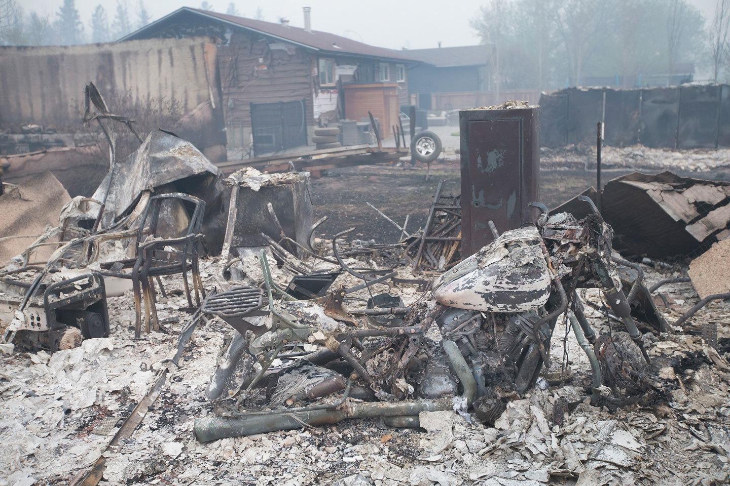 FORT MCMURRAY, AB - MAY 07:  Home foundations and skeletons of possesions are all that remain in parts of a residential neighborhood destroyed by a wildfire on May 7, 2016 in Fort McMurray, Canada. Wildfires, which are still burning out of control, have forced the evacuation of more than 80,000 residents from the town.  (Photo by Scott Olson/Getty Images)
