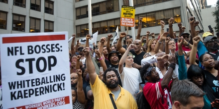 NEW YORK, NY - AUGUST 23: Activists raise their fists as they rally in support of NFL quarterback Colin Kaepernick outside the offices of the National Football League on Park Avenue, August 23, 2017 in New York City. During the NFL season last year, Kaepernick caused controversy by kneeling during the National Anthem at games to protest racial oppression and police brutality. Kaepernick is currently a free agent and some critics and analysts claim NFL teams don't want to sign him due to his public display of his political beliefs. (Photo by Drew Angerer/Getty Images)