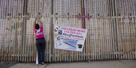 TOPSHOT - A woman hangs a banner at the wall between Mexico and US during a protest against the possibility of deportation of dreamers included in DACA program in Playas de Tijuana, Baja California, Mexico on September 4, 2017. US president Donald Trump on Tuesday could scrap the so-called DACA program that has protected from deportation some 800,000 people who arrived in the county illegally as minors. / AFP PHOTO / GUILLERMO ARIAS (Photo credit should read GUILLERMO ARIAS/AFP/Getty Images)