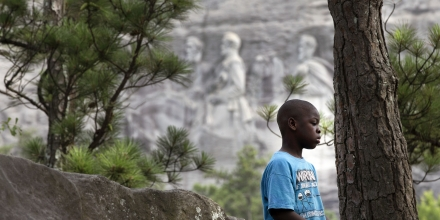 FILE - In this June 23, 2015 file photo, six-year-old Craig Stevens, of Atlanta, plays on a rock in front of the carvings on Stone Mountain in Stone Mountain, Ga. Following the deadly violence surrounding an Aug. 12, 2017, white-nationalist rally in Charlottesville, Va., a Democratic candidate for Georgia governor said the carvings should be removed. (AP Photo/John Bazemore, File)