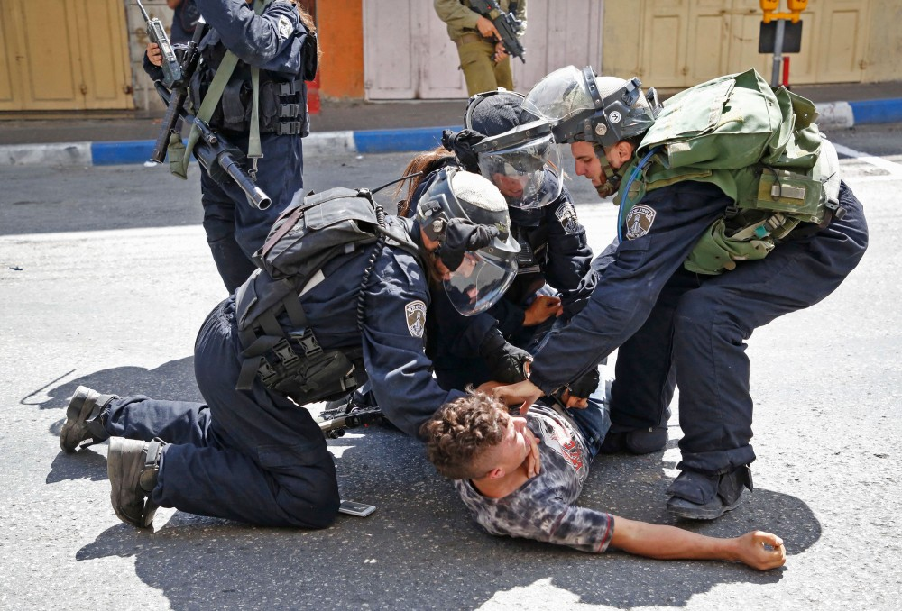 Israeli forces arrest a Palestinian youth during clashes between demonstrators and security forces in the city of Hebron in the Israeli-occupied West Bank, on July 28, 2017, as protests erupt in support of the Al-Aqsa mosque compound after Israeli police barred men under 50 from Friday prayers in the Old City of Jerusalem.Palestinians held mass prayers outside of a sensitive Jerusalem holy site after Israeli police barred men under 50 from entering following two weeks of tensions and deadly unrest. Despite fears of violent clashes around the Haram al-Sharif compound, known to Jews as the Temple Mount, the area was largely calm following Friday's midday prayers. / AFP PHOTO / HAZEM BADER (Photo credit should read HAZEM BADER/AFP/Getty Images)