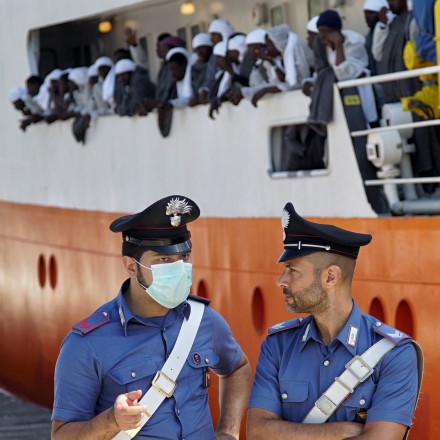 Two port security officers stand in front of the 'Aquarius' vessel as migrants wait for disembarking after arriving to Messina, Sicily island, Italy, Sunday. June 26, 2016. A group of more than 650 migrants arrived in Messina after being rescued on the Mediterranean Sea earlier this week. (AP Photo/Bram Janssen)