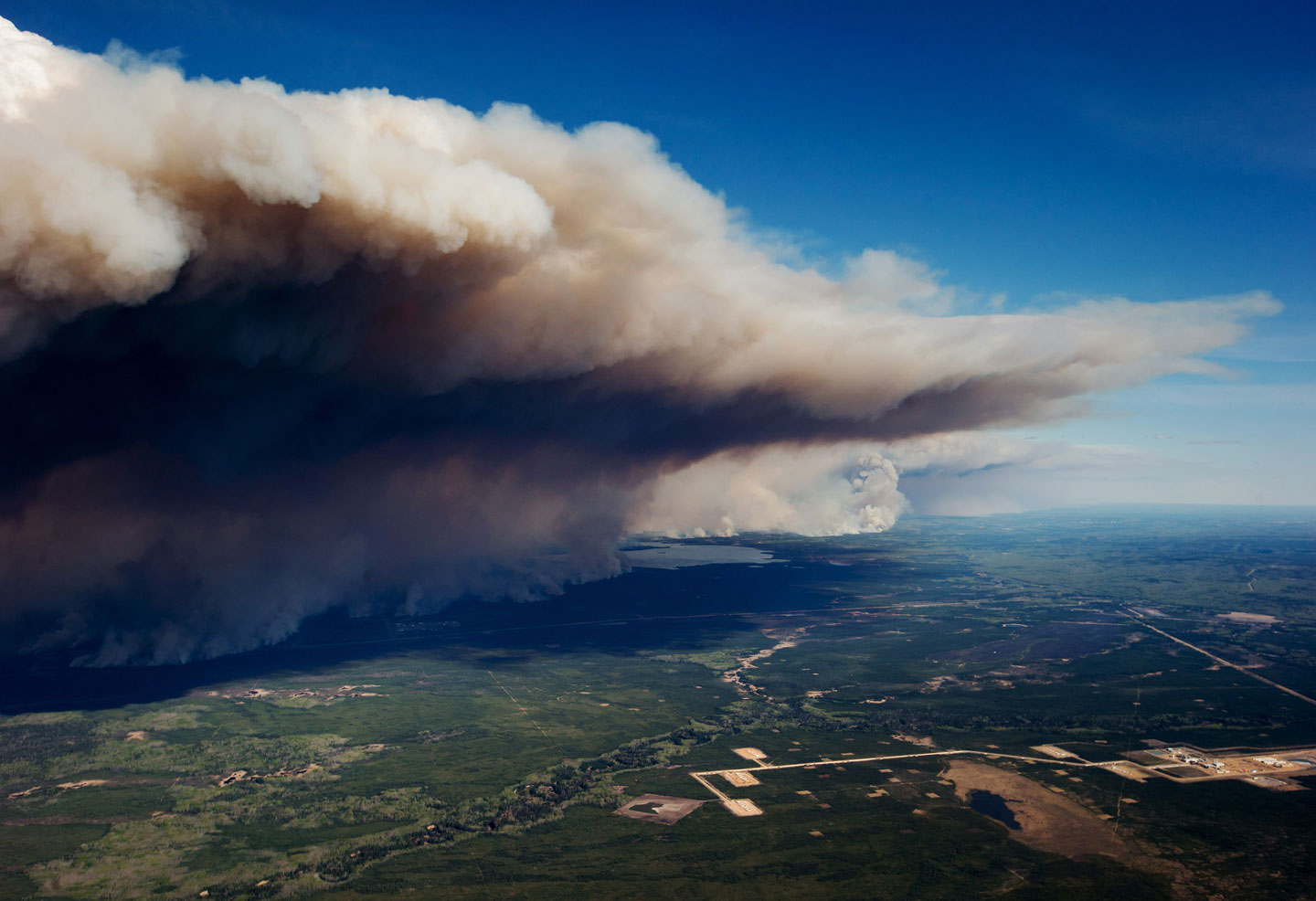A huge plume of smoke from wildfires burning rises over Fort McMurray in this aerial photograph taken in Alberta, Canada, on Friday, May 6, 2016. The wildfires ravaging Canada's oil hub in northern Alberta have rapidly spread to an area bigger than New York city, prompting the air lift of more than 8,000 evacuees as firefighters seek to salvage critical infrastructure. Photographer: Darryl Dyck/Bloomberg via Getty Images