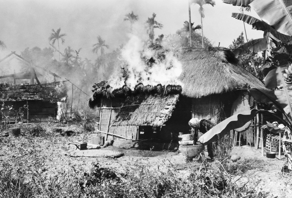An old Vietnamese woman reaches into large jar to draw water in an attempt to fight flames consuming her home in a village 20 miles southwest of Da Nang, South Vietnam on Feb. 14, 1967. (AP Photo)