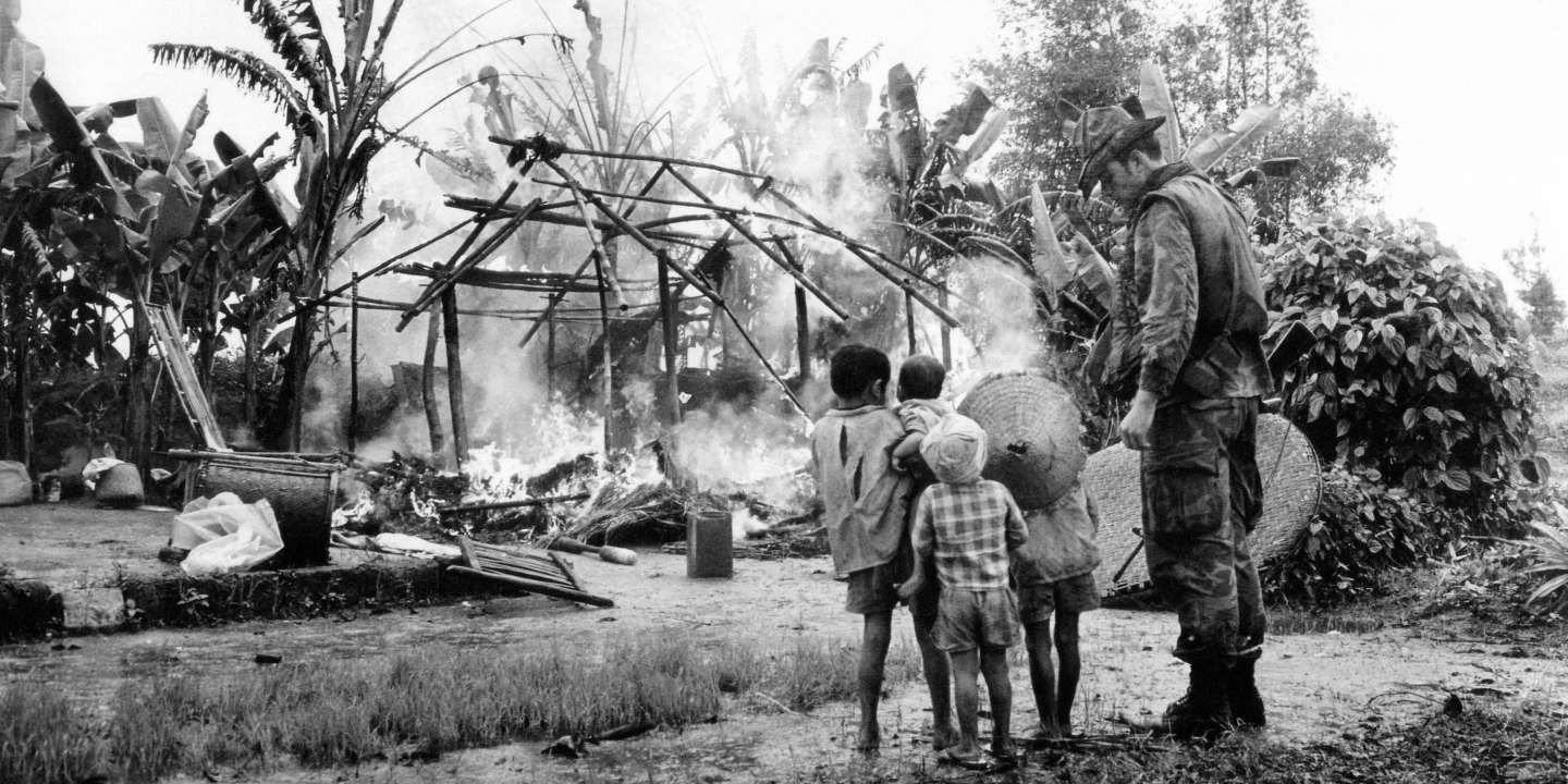 U.S. Marine stands with Vietnamese children as they watch their house burn after an Allied patrol set it ablaze after finding communist AK-47 ammunition, Jan. 13, 1971. Patrol made up of U.S. Marines and South Vietnamese popular forces searched the village, 25 miles south of Da Nang. (AP Photo/HJ)