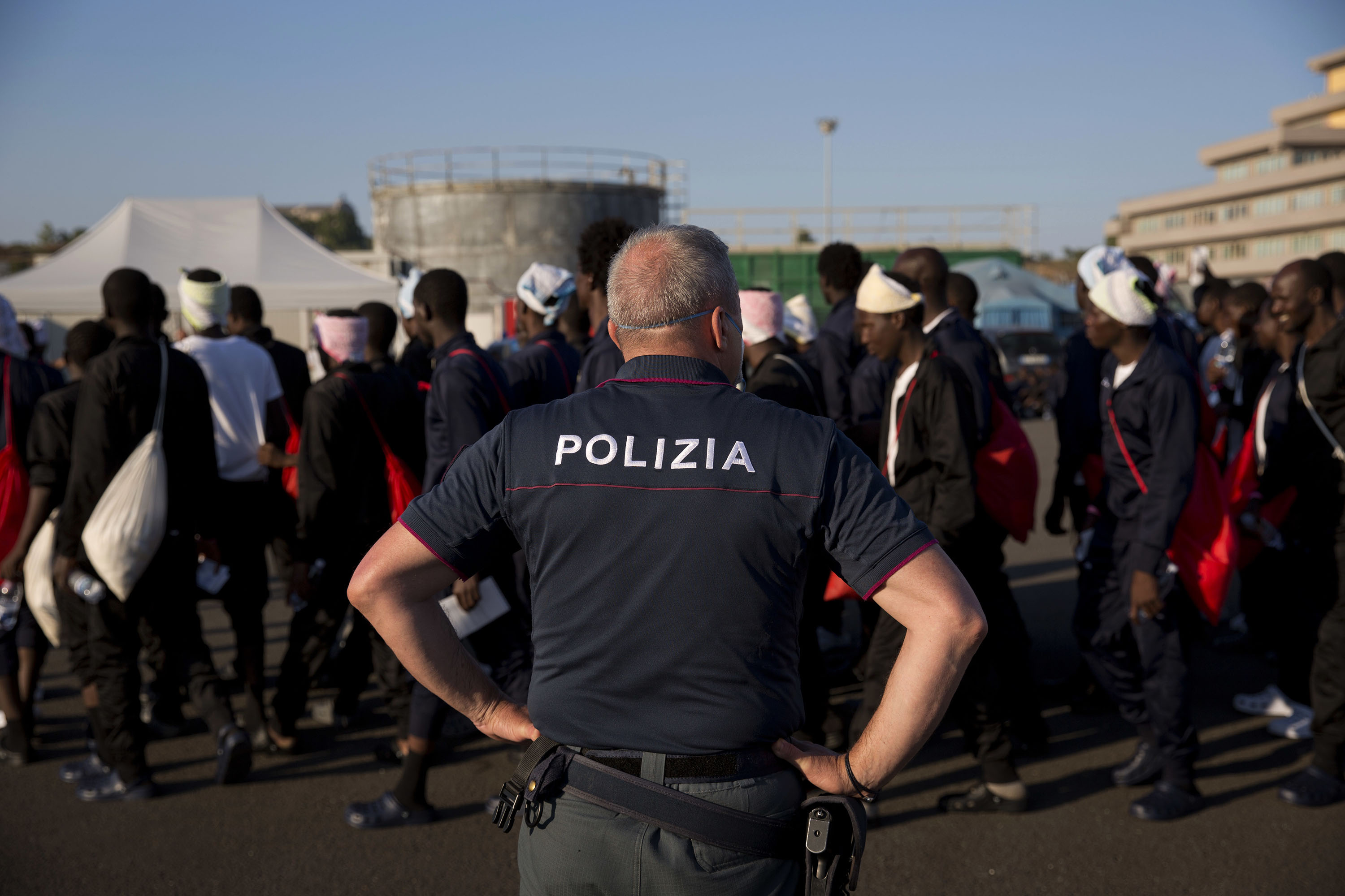 An Italian border police officer escorts sub Saharan men on their way to a relocation center, after arriving in the Golfo Azzurro rescue vessel at the port of Augusta, in Sicily, Italy, with hundreds of migrants aboard, rescued by members of Proactive Open Arms NGO, on Friday, June 23, 2017. (AP Photo/Emilio Morenatti)