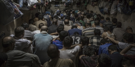 Over 80 suspected Islamic State militants are packed into a makeshift cell close to Mosul, Iraq, 07 June 2017. Many are held there for several weeks, with single bags along the walls holding their possessions. Suspects were told by Iraqi forces to face away from the camera to protect their identities. Photo by: Andrea DiCenzo/picture-alliance/dpa/AP Images